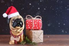 一条狗的图在圣诞节帽子的在一张木桌 来年的标志 库存照片