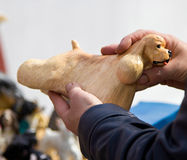 一条狗的小雕象在买家的手上 库存照片