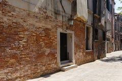 一条狭窄的威尼斯街道的典型的看法在夏天晴天 红砖大厦 免版税库存照片