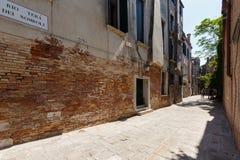 一条狭窄的威尼斯街道的典型的看法在夏天晴天 红砖大厦 库存照片