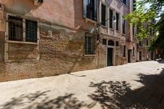 一条狭窄的威尼斯街道的典型的看法在夏天晴天 红砖大厦 免版税图库摄影