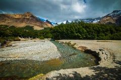 一条狭窄的河从森林流动和山和轮 Shevelev 免版税库存图片