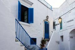 一条狭窄的街道和在t的蓝色窗口的看法有一个蓝色门的 库存照片