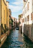 一条狭窄的运河的看法在有一条小船的威尼斯在边 库存照片