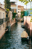 一条狭窄的运河的看法在有小船的威尼斯在边停泊了 图库摄影