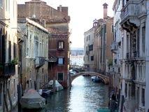 一条狭窄的运河的风景在有小船的威尼斯由大厦停放了 库存照片
