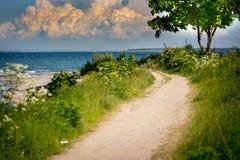 一条狭窄的道路导致海滩从海 库存图片