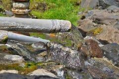 一条生锈的管道的末端用流动入自然小河的热的地热水在冰岛自然公园 免版税库存图片