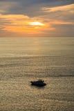 一条电动机转速的小船的剪影在日落期间的 库存照片