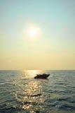 一条电动机转速的小船的剪影在日落的 图库摄影