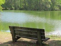 一条疲倦的老长凳由一条平静的水路提供一个休息处 图库摄影