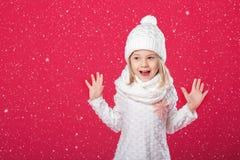 一条白色帽子和围巾的小微笑的白肤金发的女孩在红色backg 库存照片