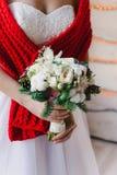 一条白色礼服和红色围巾的新娘有花束的 免版税库存图片