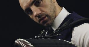 一条白色衬衣和灰色领带的手风琴师 黑背景的音乐家在演播室 股票录像