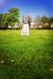 一条白色裙子和牛仔布夹克的女孩享受一个晴天的 免版税库存图片