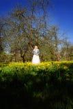 一条白色裙子和牛仔布夹克的女孩享受一个晴天的 免版税库存照片