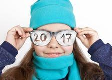 一条盖帽和围巾的快乐的女孩在与题字的滑稽的玻璃2017年 库存图片