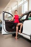 一条短裙和一辆白色汽车的美丽的女孩 免版税库存照片