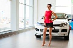一条短裙和一辆白色汽车的美丽的女孩 免版税图库摄影