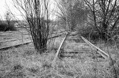 一条离开的和被放弃的铁路的Dystopic图象 库存照片