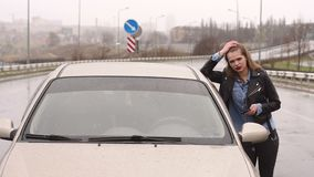 一条空的多雨路的一个女孩请求通过汽车的帮助和中止 股票视频