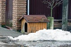 一条空的狗在随风飘飞的雪的篱芭附近流洒了 免版税库存图片