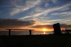 一条空的长凳和河在日落的公园 免版税库存图片