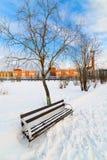 一条空的长凳在积雪的城市公园。 免版税库存照片