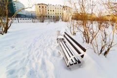 一条空的长凳在积雪的城市公园 免版税库存图片