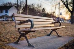 一条空置长凳在日落的一个公园 库存照片