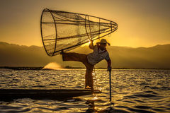 一条竹小船的缅甸渔夫在日出 免版税库存照片