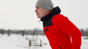 一条粗呢夹克和黑长裤的一年轻帅哥在一个开放平台的冬天执行otshimaniya  股票视频