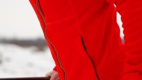 一条粗呢夹克和黑长裤的一年轻帅哥在一个开放平台的冬天执行otshimaniya  股票录像