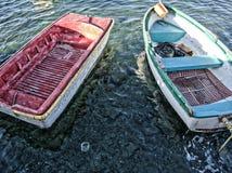 一条红色和一条蓝色小船紧挨着在海 免版税库存照片