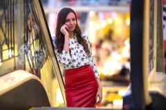 一条红色皮革裙子和一件女衬衫的一名妇女有在的样式的 免版税库存图片