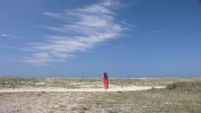 一条红色裙子的一个女孩在含沙地面上走反对一不尽的天空蔚蓝的背景 影视素材