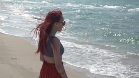 一条红色裙子的慢动作红发年轻女人在海滩站立并且看海浪 股票视频