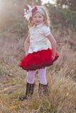 一条红色裙子的逗人喜爱的女孩 免版税库存照片