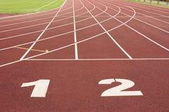 一条红色赛马跑道的车道与数字的在体育场内 库存图片