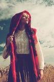 一条红色围巾的女孩在领域 免版税库存照片