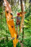 一条绳索路线的青少年的男孩在通过垂悬的绳索障碍的树梢冒险公园 免版税库存图片