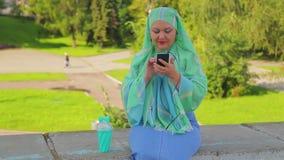 一条绿色围巾的一名年轻回教妇女在公园喝咖啡并且是在messenge 股票视频