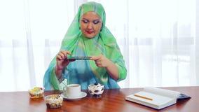 一条绿色围巾的一名年轻回教妇女在咖啡馆在电话的照片酥皮点心 影视素材