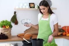 一条绿色围裙的年轻西班牙妇女烹调在厨房里的 主妇发现了她的汤的一份新的食谱 什么是它  库存图片