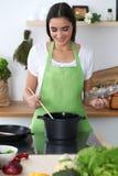 一条绿色围裙的年轻西班牙妇女烹调在厨房里的 主妇发现了她的汤的一份新的食谱 免版税库存图片