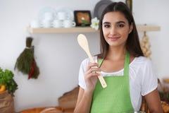 一条绿色围裙的年轻西班牙妇女烹调在厨房里的 拿着木匙子的主妇,当微笑时 免版税库存照片