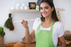 一条绿色围裙的年轻西班牙妇女烹调在厨房里的 拿着木匙子的主妇,当微笑时 库存照片