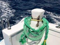 一条绿色强的耐久的重织品船绳索,停泊处的,中止一条绳索附加船,在背景的一条小船  库存照片