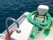 一条绿色强的耐久的重织品船绳索,停泊处的,中止一条绳索附加船,在背景的一条小船  免版税图库摄影