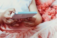 一条美丽的蓬松桃红色裙子的小女孩小女孩有皱纹的使用白色手机 免版税库存图片